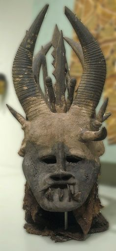 Some Igbo use large funeral masks that have human and animal features. This helmet has a basketry cap upon which is formed a head of wood and black gum; animal teeth, horns and wooden blades are present. The mask's dist Art Chinois, Art Tribal, Atelier D Art, Art Premier, Art Africain, Art Japonais, Animal Masks, Masks Art, Edgar Allan Poe
