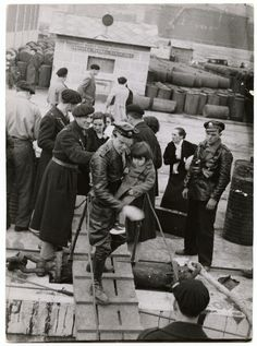[Man carrying child aboard evacuation ship, Bilbao]