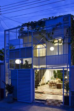 "Constructed on a limited budget, the house was designed to both ""look green"" and fit in with its neighbours. The architects at a21studio used steel beams to construct a basic framework, then clad the exterior with lightweight mesh and corrugated panels, and encouraged plants to grow up around it. By Vietnamese architects a21studio 