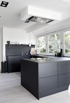 We really love the use of materials in the kitchen, black, wood and a hint of brass. And because of all the windows in the room, it's not a dark space at all.