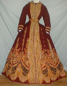 """A truly magnificent 1860s burgundy cashmere wool paisley print dress that has documentation.  The old note reads """"Paisley dress worn by Grandma Eckert at mother's wedding.""""  The paisley pattern is designed in shades of orange, blue, and black.  The dress has a paisley print belt and the armscyes and neck are piped."""