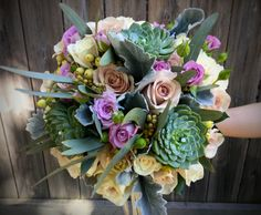Roses, spray roses, dusty miller, eucalyptus and succulents. Beautiful bride's bouquet.