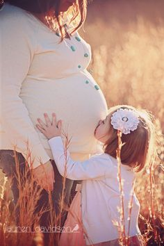 Maternity photography with older siblings. Pregnancy pictures in field at sunset with toddler in cowboy boots. Maternity portrait in the winter or summer with ivory and turquoise. Unique maternity pictures with daughter toddler.