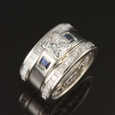 Custom designed wide-band diamond celebration ring, featuring delicate bezel set sapphire accents.
