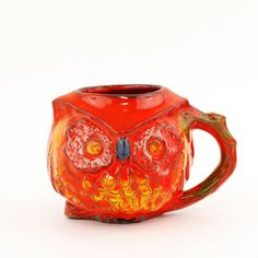 An adorable stoneware wide eyed owl figural pottery mug by Bennett Welsh Designs dated 1969. Features a rich colorful background mix of red, orange