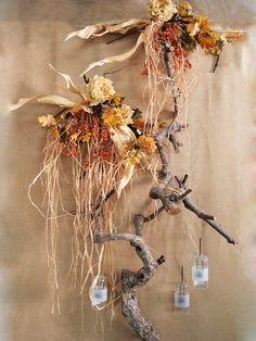 Decorazione autunnale a parete con tronchi e stecchi di legno, fiori artificiali, rafia, bacche e fioglie secche. La composizione è realizzata su uno sfondo vetrina di juta, che rende la nostra idea molto rustica e con un tocco shabby chic. Le lanterne porta candela o porta tealight daranno luce a questa splendida vetrina autunnale fai da te. Acquista tutto l'occorrente per le tue vetrine direttamente online nel nostro shop all'ingrosso.