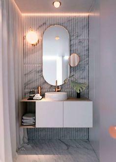 miroir lumineux salle de bain en forme ovale avec un petit miroir rond supplémentaire et un meuble suspendu
