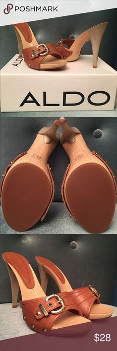 Brand New Aldo Tan Mule Heel Sandals Brand new with original box. Aldo slip on tan heels. Leather upper with gold buckle detail. Heel has a gloss tint to it and a wooden sole. Style: Spells. Size 38. Aldo Shoes Heels