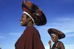 Did you know that the biggest South African population group is the Zulu? The Zulu mainly live in rural settlements in KwaZulu-Natal and have a king.  This photo shows two Zulu women wearing a traditional conical headdress of married women, the isicolo. It is woven from their own hair, but nowadays hair extensions are often woven over a grass frame.