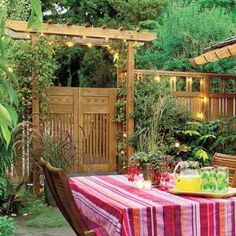 A custom fence with an arbor-topped gate intersects the side of an existing outbuilding, adding a sense of intimacy to this outdoor dining space. | Photo: Norm Plate | thisoldhouse.com