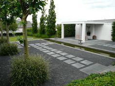 Een zeer strakke tuin en een minimalistische overkapping met haard. Het tuinontwerp is gevormd met een strakke langwerpige vijver, grindbedden, staptegels en knotplatanen.