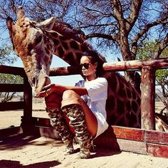 Rihanna and a giraffe. Long Boots && Shirt, with short shorts