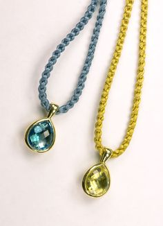 Two of our 18KT yellow gold pendants, set with pear shape gemstones and housed on a silk cord; one with a Blue Topaz, and one with a Citrine