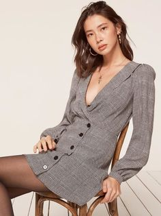 Your button-down is now a dress. This is a mini length, button front dress with a low v neckline, a shawl collar and a drapey bodice.