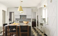 Kitchen with pinwheel tile backsplash, white cabinets and drawers, black and white checkered floor, brass pendant lights over and island surrounded by wood bar stools with leather cushions