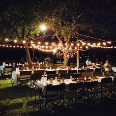 Wedding idea with string lights and multiple decorated tables for guests