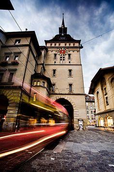 A tram passes under a clock tower in Bern Old Town, Bern, Switzerland.