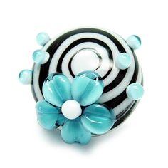 Alexiss Glas Button - schwarzer Druckknopf mit weißen Streifen und blauer Blüte