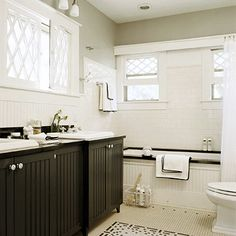 Small Bath with a Detailed Design-This small bath illustrates the value of a detail-rich design. With its diamond lattice window shutters, 1-inch-square black-and-white floor tiles, and beaded-board bathroom vanities and bathtub surround, this bath manages to be big on affordable architectural style even if it is small on square footage.