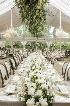 long mirror top table floral fixture above wicker runner modern tented reception wedding garden