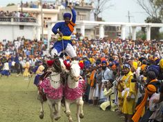PUNJAB: A day after Holi, the state celebrates Hola Mohalla (25–27 March 2016, this year), an annual Sikh festival with music, poetry, martial-arts display and stunts like balancing oneself on two fast-moving horses.  Photo: Jiti Chadha/Demotix/Corbis #travel #celebrate #India #adventure #colours