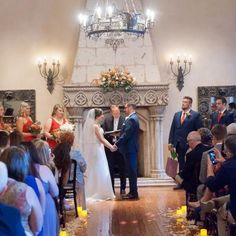 Indoor wedding ceremony in Chianciano with rose petals and candles lining the aisle to the stone fireplace | Leslie Ann Photography | villasiena.cc
