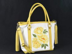 White and Yellow Roses Leather Bag. Bright, cheerful and joyful are what come to mind when thinking of yellow roses. Yellow roses create warm feelings and promote happiness. Giving yellow roses can tell someone the joy they bring you and the friendship you share. This gardener's delight, roomy tote bag is made of creamy white, buttery soft genuine leather with accents of delicious sunshine bright yellow leather accoutrements'. The interior lining of complimenting floral...