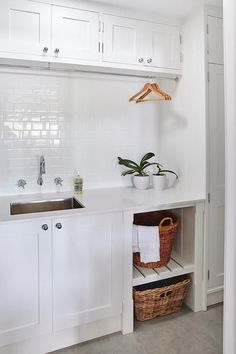 Monochromatic white laundry room boasts white slatted shelves holding woven baskets beside white cabinets adorning polished nickel knobs and a white quartz countertop framing a stainless steel sink positioned below a wall mounted polished nickel faucet kit fixed to a white subway tiled backsplash beneath a tension rod drying rack mounted under white overhead cabinets.