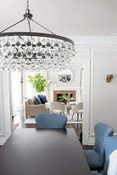 A black dining chair surrounded by blue wingback dining chairs is illuminated by a Robert Abbey Bling Oval Chandelier.
