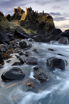 Dunluce Castle, County Antrim the ruins have a desolate grandeur as they rise dramatically from basaltic rock standing over a hundred-feet sheer above the wild and chill sea. Separated from the mainland by a deep chasm crossed only by a narrow bridge and penetrated below by a long cave, this precarious rocky outcrop occupied a position of great strategic importance that was fought over for centuries, eventually becoming, in the sixteenth century, the principal stronghold of the McDonnells.