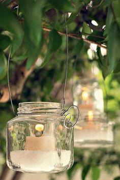 Preso por um arame e pendurado no galho da árvore, o pote recebeu pedrinhas de sal grosso e uma vela. O sal pode ser substituído por água. A ideia impressiona em qualquer encontro ao ar livre