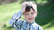Close-up of a grade schooler standing outdoors holding his hand to his head