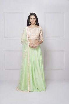 Peach and Teal green Lehenga Set. It features a pastel pink fully embroidered blouse with green dupatta and a pastel green raw silk lehenga with heavy flare.