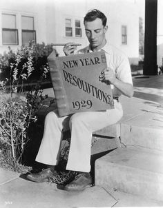 "Buster Keaton      Publicity shot of Buster Keaton on MGM lot reading ""1929 New Year Resolution"" book."