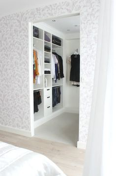 walk-in-closet. Gray and white wall design (maybe wall paper?). Cute.