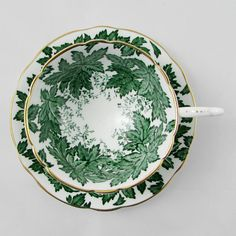 Beautiful tea cup and saucer set is made in England by Coalport. Tea cup is white with a green leaf pattern and gold trimming with matching saucer. Teacup and saucer in excellent condition (see photos). Markings read: Coalport Bone China Made in England AD 1750 Please bear in mind