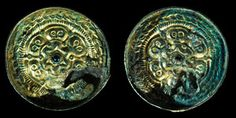 6th century AD. A matched pair of applied disc brooches, each a cast discoid plate with fabricated rim; inserted repoussé plaque with outer band of ropework, billetted band and six helmetted faces surrounding a rosette with central cabochon black glass stud; pin-lug and catchplate to the reverse.