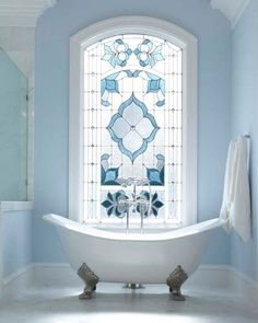 Bathroom- claw foot bath with beautiful baby blue stained class window