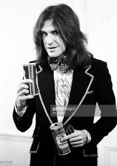 Ray Davies of The Kinks poses backstage wearing a blazer and bow tie and holding two cans of beer at Newcastle City Hall in October 1973.