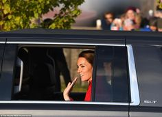 Windows rolled down, the Duchess of Cambridge waved to well-wishers as she pulled up to th...