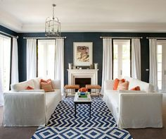 Love the dramatic navy blue walls, wide crown moulding and pops of orange.