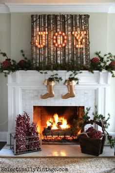 JOY Mantel - part of this fabulous Christmas House Tour! Love the metal stockings and the pine cone garland from HomeGoods on the mantel and in the wood basket eclecticallyvintage.com sponsored pin