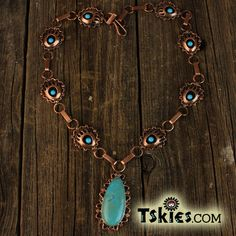 Description: The necklace features a set of 8 shadowbox turquoise bear claw design pendants measuring 3/4″ X 5/8″ connected by a handmade coper chain link. The center is finished with larger pendant with a turquoise stone measuring 1-1/2″ x 5/8″. The necklace is Copper and made by Native artist RB a member of the Navajo Tribe. The …