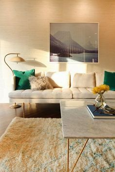 A cool and neutral living room with warm tones and green pillows