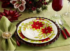 Grass Green Hemstitch Placemat • Scalloped Antiqued Wood Charger • Poinsettia Dinner Plate & Salad Plate • Poinsettia Glass Dish • Grass Green Hemstitch Napkin with Fleur Gold Rhinestone Napkin Ring • Red Sophia Flatware • Red Goblets with Clear Stem