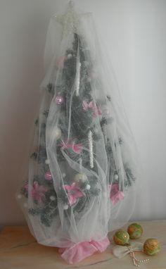 Mi bonito árbol de Navidad Shabby Chic, con flores de pascua en color 'millennial pink' envuelto con una mosquitera o velo de novia blanco que le da un aire empolvado. En la copa la estrella, y las bolas en nácar y de crista les rosa con brillantes, los témpanos  y la guirnalda de luces  blancas con envoltorio aterciopelado completan la sencilla decoración del árbol.