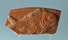 Roman terra sigillata plate fragment with fish, 4th-5th century A.D. African red slip ware plate fragment, North Africa, with fish, 8 cm long. Private collection