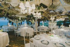 Seaside dinner wedding reception, natural elements covering the ceiling plus white chandeliers. Candelabras with tea light vases as centerpiece