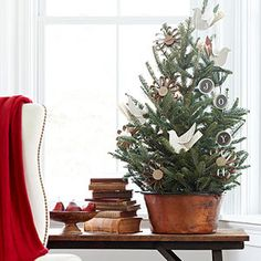 Rustic Tabletop Christmas Tree: Create an old-fashioned look for a side table with a tabletop Christmas tree in a copper pot. Adorn the tree with simple paper ornaments and display next to a stack of old books for rustic character. Christmas Tree Base, Tabletop Christmas Tree, Little Christmas Trees, Beautiful Christmas Trees, Holiday Tree, Rustic Christmas, All Things Christmas, Christmas Tree Decorations, Christmas Holidays