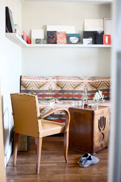 A lovely small Paris nook: Blanket covered futon, small chair and a vintage radio set as a table. A high shelf provides display and storage.